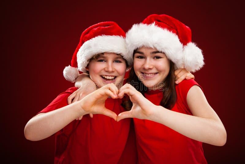 Jultid - flickan och pojken med Santa Claus Hats visninghjärta undertecknar fotografering för bildbyråer
