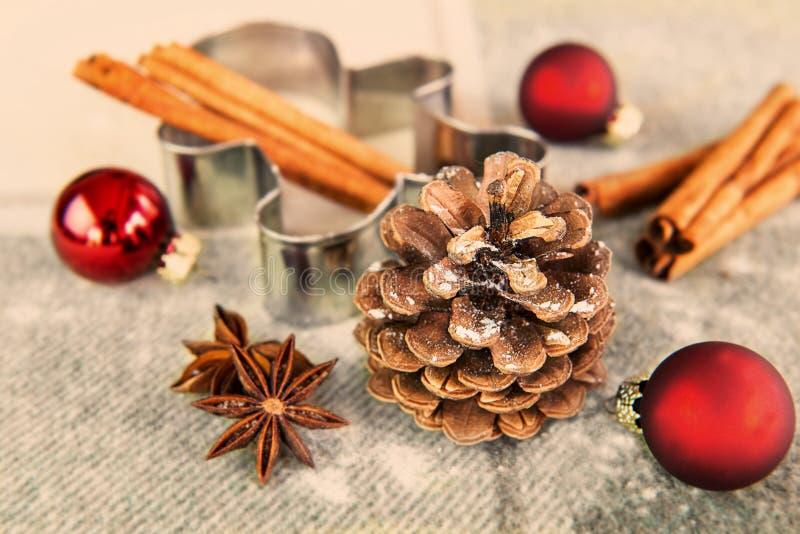 Jultid - pinecone, pepparkakaform, julbollar arkivbild