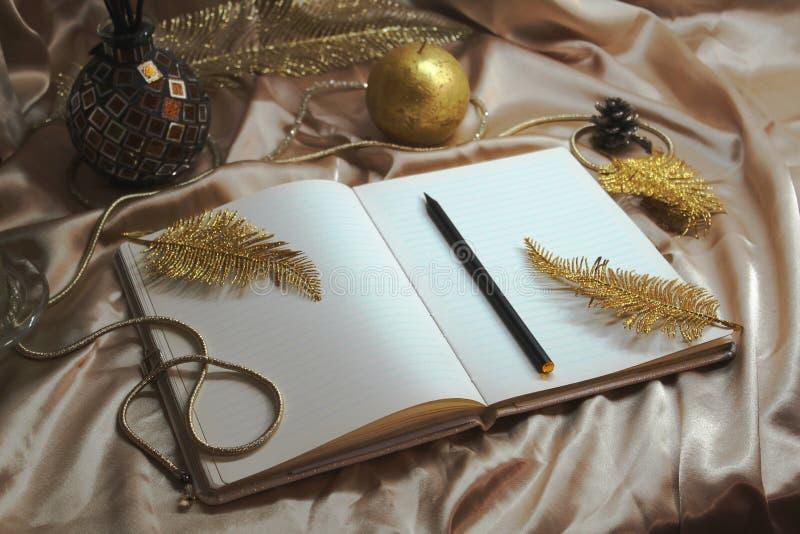 Jultid, xmas-dekoration, gott nytt år 2020, gyllene anteckningsbok, bucket list, för att göra lista och planer, ljus på bordet arkivfoto