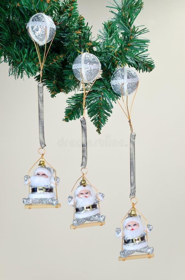 Jultomte dockor på gungor royaltyfri bild