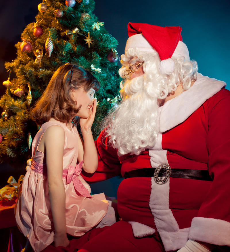 Jultomte och liten flickainnehavgåva arkivbilder