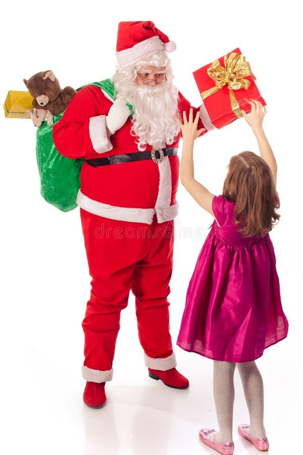 Jultomte som ger gåvaliten flicka arkivbild
