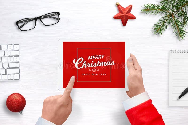 Jultomten arbetar för att överföra att hälsa post med minnestavlan arkivbilder