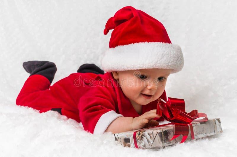 Jultomten behandla som ett barn flickan som ligger på den vita filten med gåvan arkivbild