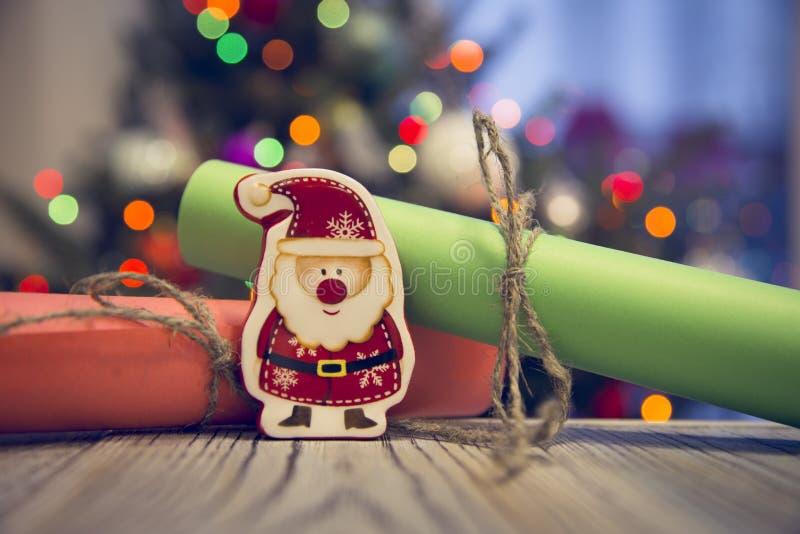 Jultomten för en leksak på en trätabell mot den dekorerade julgranen arkivfoton