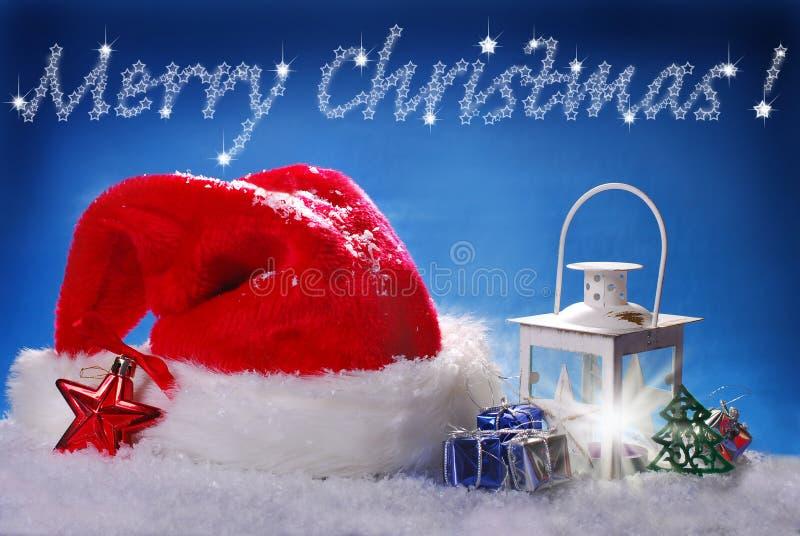 Jultomten hatt och jultappninglykta på snö royaltyfri fotografi