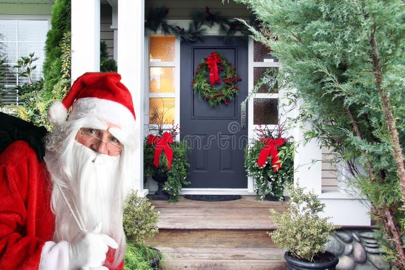 Jultomten med gåva på ytterdörren royaltyfria foton