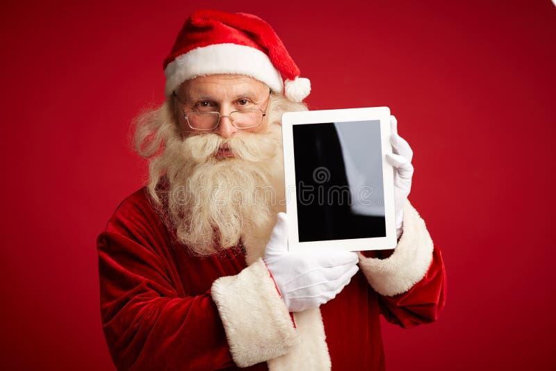 Jultomten med touchpaden royaltyfri foto