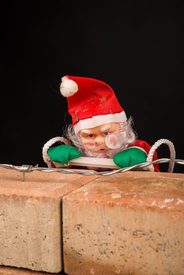 Jultomten som försöker att klättra väggen arkivbilder