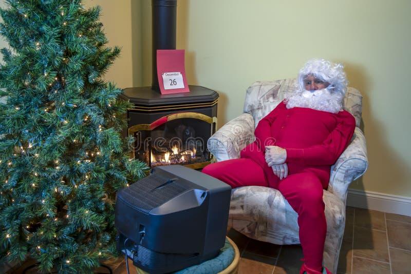 Jultomten som håller ögonen på TV efter jul royaltyfri fotografi