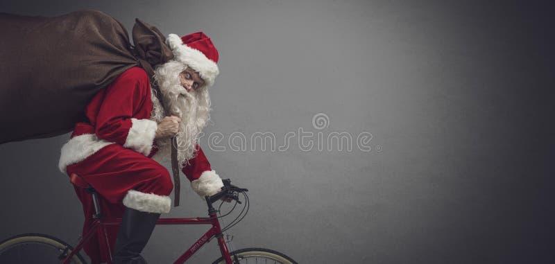 Jultomten som rider en cykel och bär gåvor arkivbild