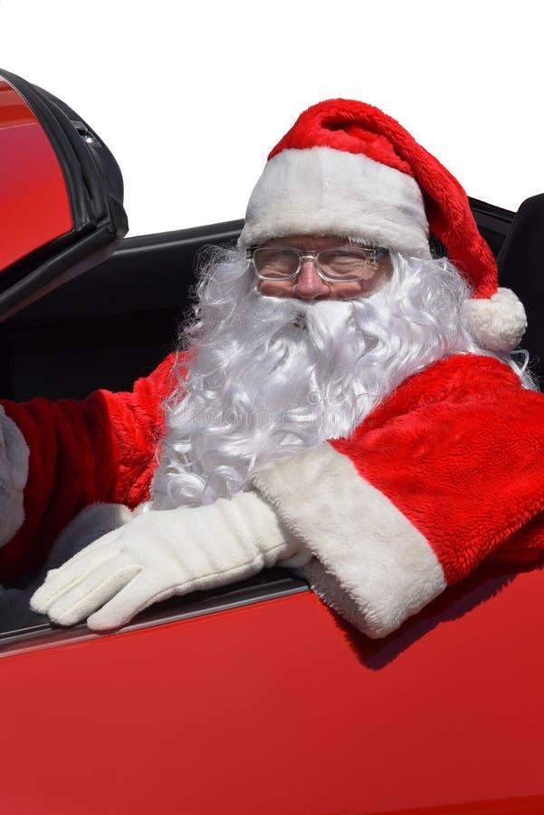 Jultomten som sitter bak hjulet av en röd sportbil arkivfoton