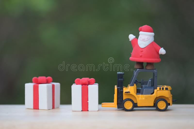 Jultomten som står på gaffeltrucken som laddar klart för gåvaask som överförs till barn royaltyfri bild