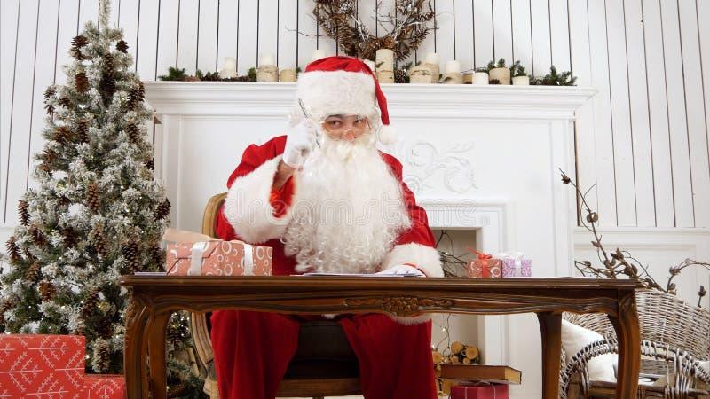 Jultomten som svarar bokstäver i hans seminarium och förklarar vad den ` s gillar för att vara jultomten fotografering för bildbyråer