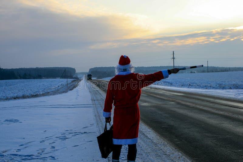 Jultomten stoppar bilen med en polistaktpinne royaltyfri fotografi