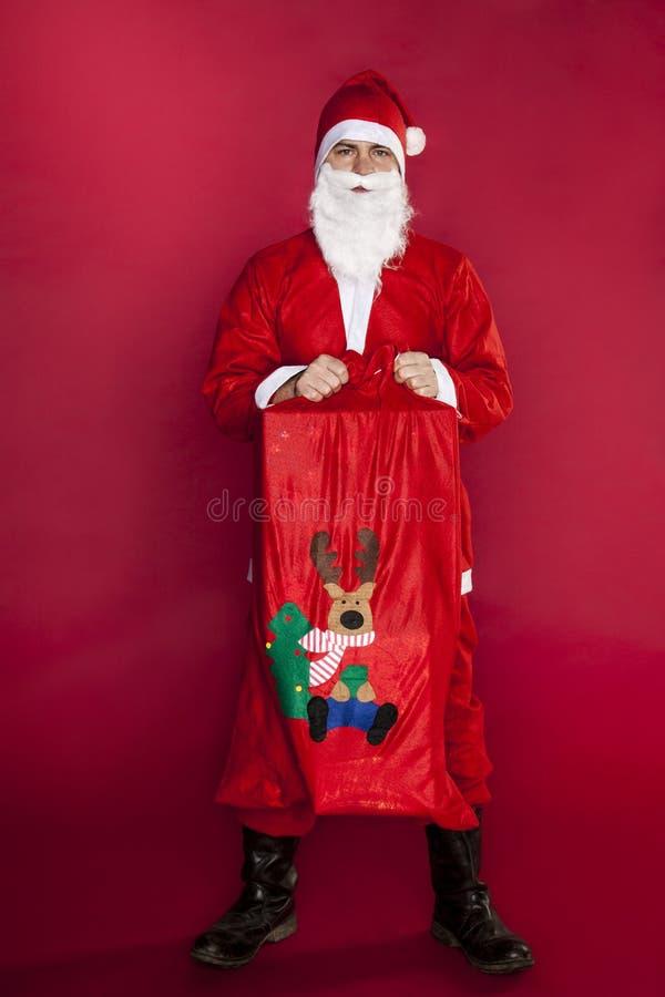 Jultomten väljer upp en gåvapåse, en stor påfyllning arkivfoton