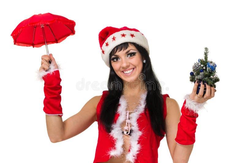 Jultomtenflicka med ett paraply och en julgran mot isolerad vit arkivfoton