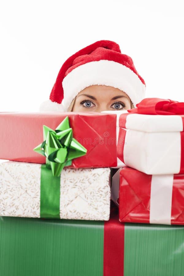 Jultomtenflickanederlag bak gåvorna royaltyfri bild