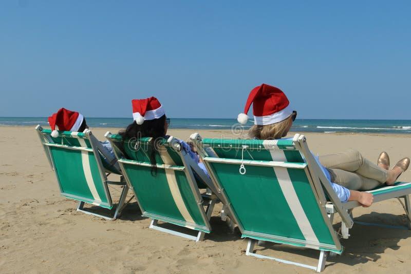 Jultomtenflickor på en solig strand royaltyfri foto