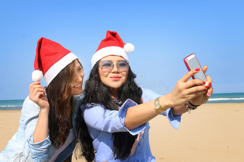 Jultomtenflickor tar selfie på en solig strand royaltyfria foton