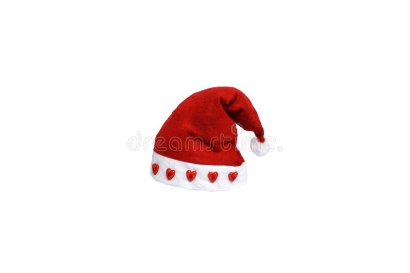 Jultomtenhatt med röd hjärta på pälsen, festival för glad jul, isolerad vit bakgrund royaltyfri bild