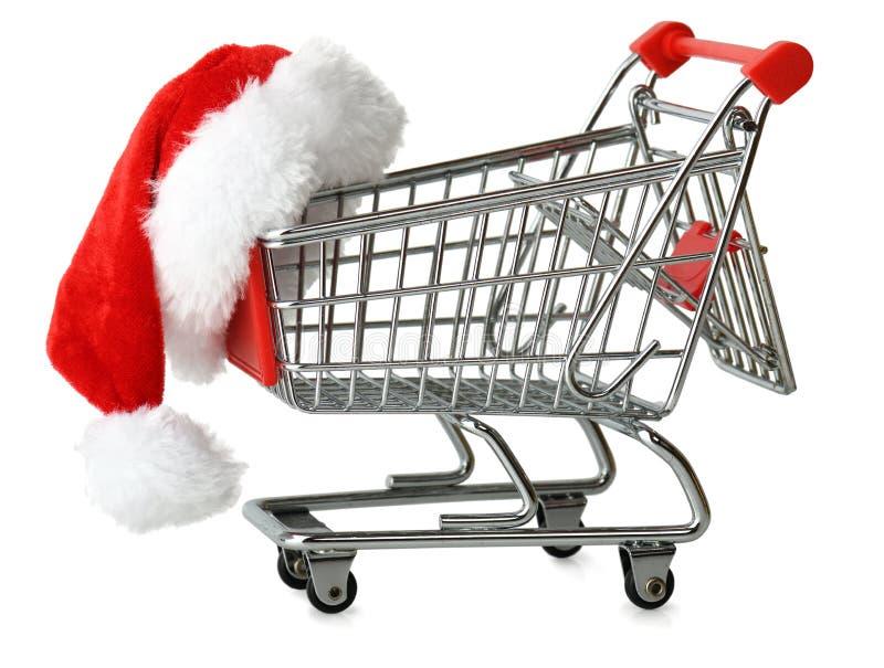 Jultomtenhatt på en shoppingvagn royaltyfri foto