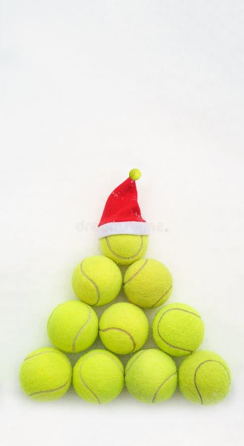 Jultomtenhatt på tennisboll på vit snöbakgrund Jul och begrepp för nytt år med tennisbollar Gul tennis för grön färg royaltyfria bilder