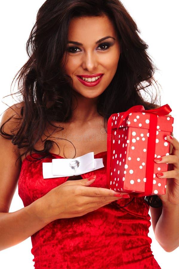Jultomtenhjälpredaflicka på vit bakgrund med långt hår och röd gif arkivfoton