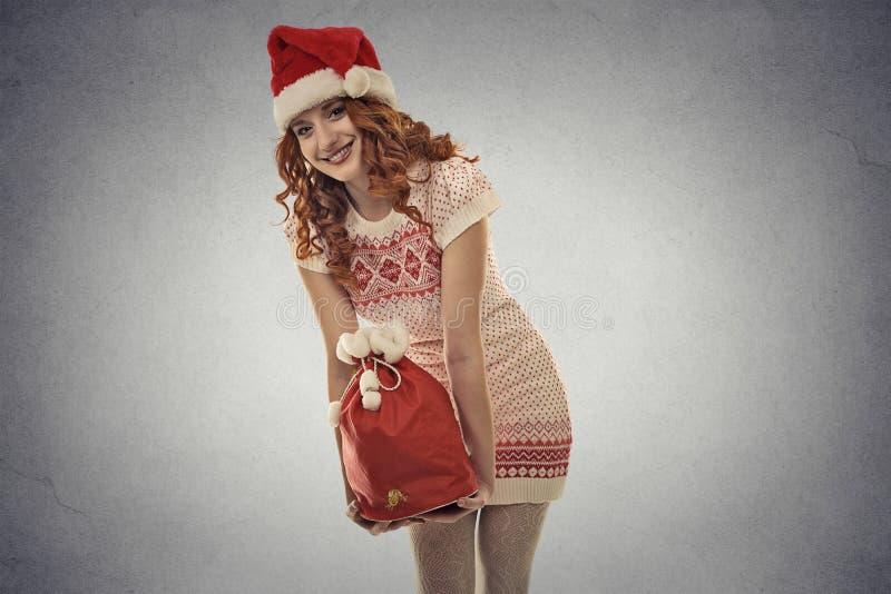 Jultomtenhjälpredaflickan som bär stor röd jul, plundrar mycket av gåvor royaltyfria foton
