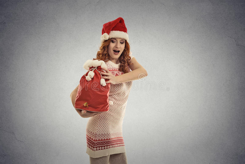 Jultomtenhjälpredaflickan som bär stor röd jul, plundrar mycket av gåvor royaltyfria bilder