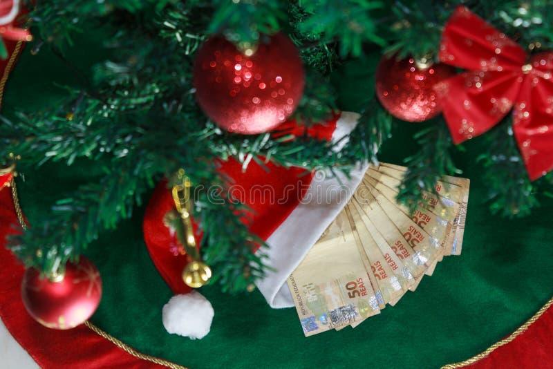 Jultomtenlock med pengarbrasilianen Pengar för julgåvor eller gåvapengar Julfilial och klockor royaltyfria foton