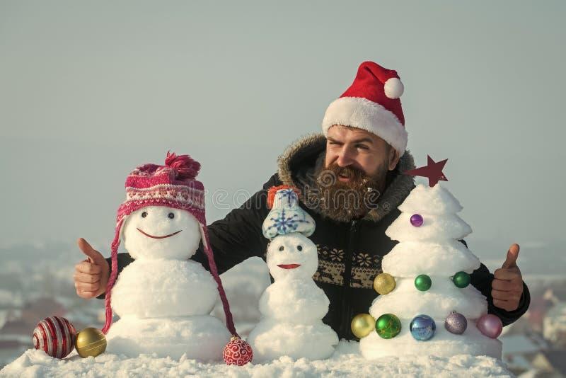 Jultomtenman som blinkar med snöig skulpturer fotografering för bildbyråer