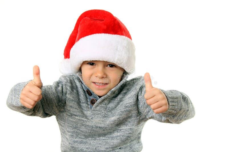 Jultomtenpojke med tummar upp arkivfoton