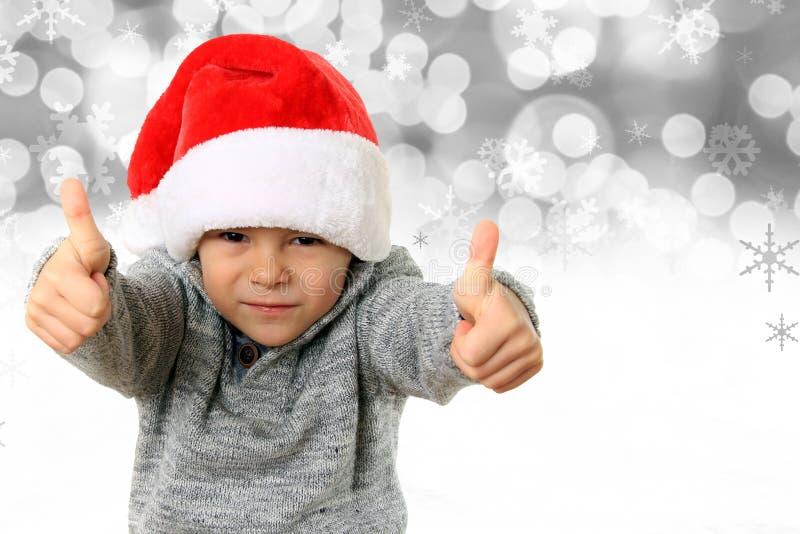 Jultomtenpojke med tummar upp royaltyfria bilder