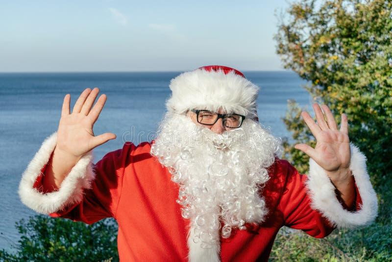 Jultomtensemester på havet Traditionell röd dräkt och koppla av på stranden arkivfoto