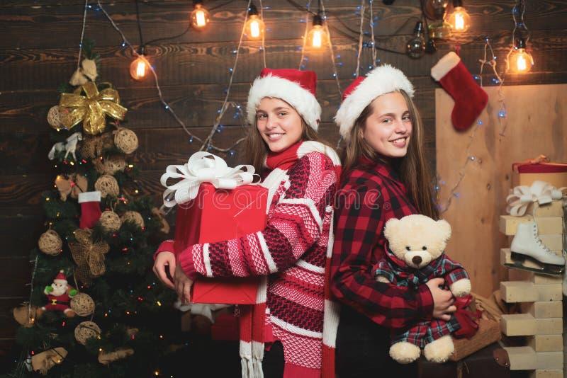 Jultonåringar Liten flicka med en julklapp på träbakgrund Innehåller genomskinliga objekt Ungen tycker om ferien arkivbilder