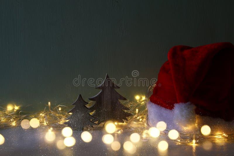 julträdet med girlanden tänder bredvid den santa hatten arkivfoton