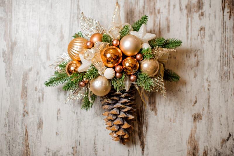 Julvägggarnering som göras av grankotte med guld- kulöra bollar arkivbilder