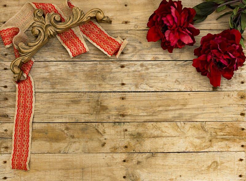 Julvykortram på träbakgrund för hälsningkort Rött band med tappningträprydnaden och stora blommor xmas arkivbild