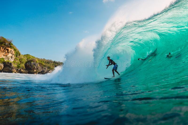 July 29, 2018. Bali, Indonesia. Surfer ride on barrel wave. Professional surfing in ocean at big waves royalty free stock photos