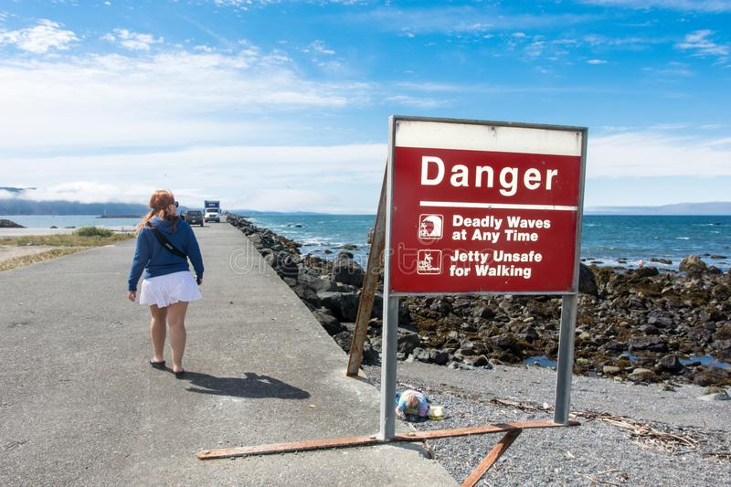 CRESCENT CITY CA: Despite the warning on the sign not to walk on the jetty, a female tourist ignores the sign, stock photos