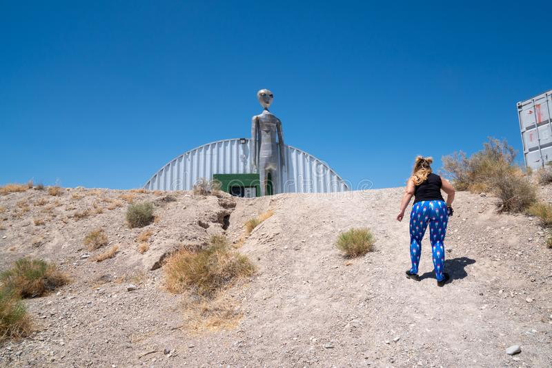 JULY 4 2018 - RACHEL, NV: Adult female walks toward an alien statue. Concept for alien abduction stock photo