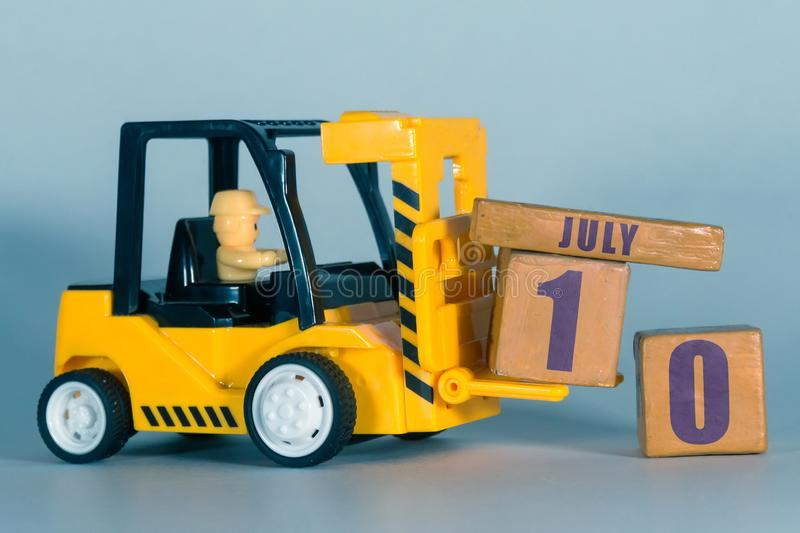 July 10th. Day 10 of month, Construction or warehouse calendar. Yellow toy forklift load wood cubes with date. Work planning and. Time management. summer month stock photo
