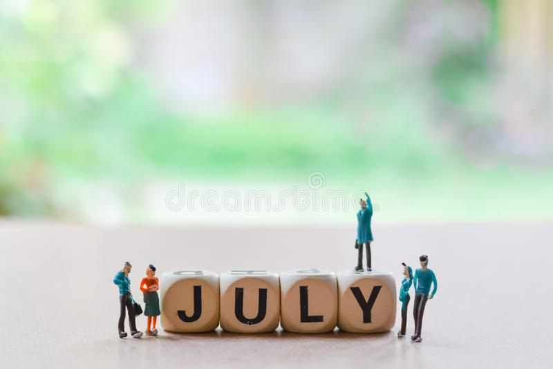 July on wooden block with Couple love of miniature people, small model human figure standing on floor with green blurry background royalty free stock photography