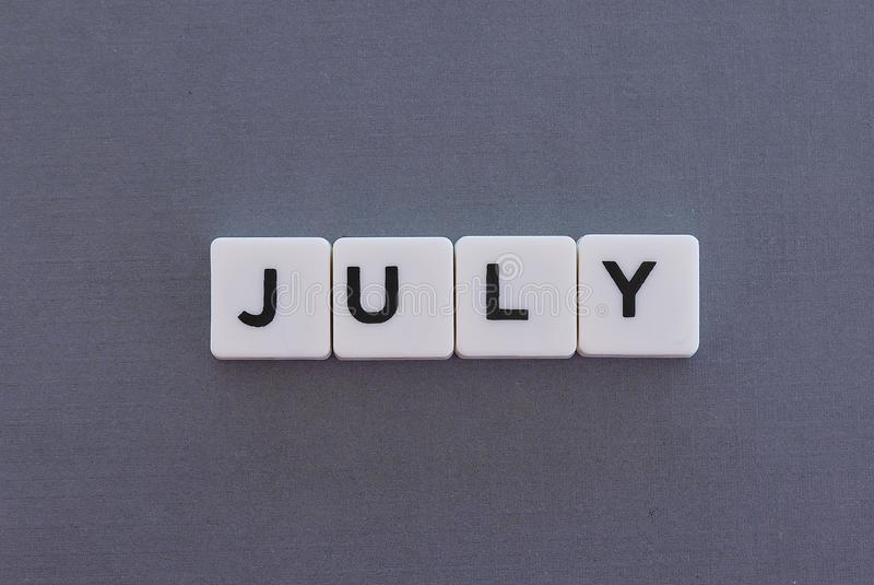 July word made of square letter word on grey background. Month time day date monthly calendar concept text summer reminder design number hello diary holiday stock image