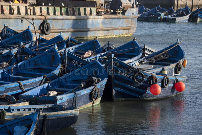 jumble of small blue fishing boats huddled together  in port stock photo