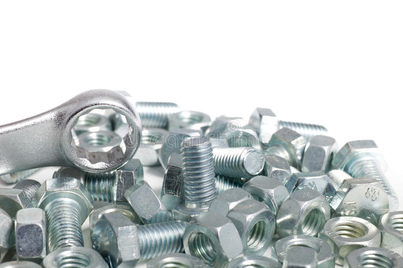 Jumbled pile of bolts and nuts. Jumbled pile of silver steel bolts and nuts with a ring spanner isolated on a white background with copyspace stock images