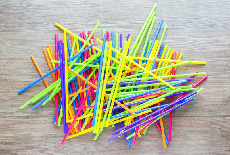 Jumbled pile of colorful plastic straws. A jumbled pile of colorful plastic flexible straws spread out on a wooden table stock images