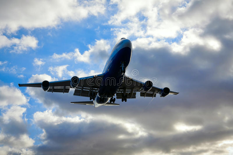 Jumbo Jet 747 Passing By Overhead royalty free stock image