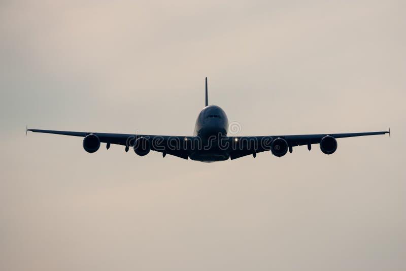 Jumbon för flygbussen A380 - spruta ut flygplanflyget i frount av molnig himmel royaltyfria foton